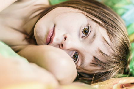 Baby lying in bed in the morning. Stock Photo