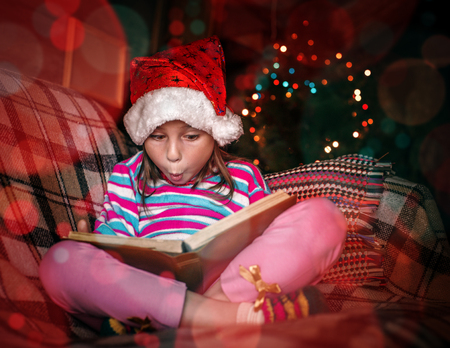 surprisingly: Surprised young girl in a Christmas hat with a book.