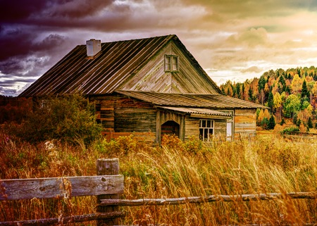Old house in an overgrown grass in autumn day.