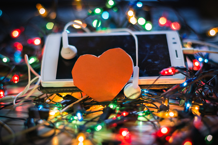 Headphones and smartphone on the table to listen to holiday music. Stock Photo