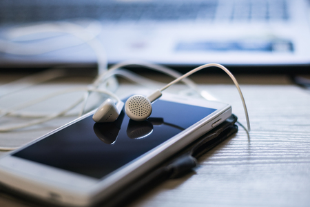 Office desk with mobile phone and headphones. Stock Photo