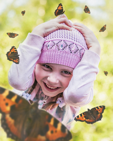 Child clutching her head among the hovering butterflies. Stock Photo