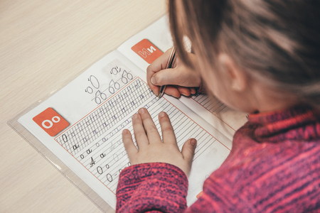 Close up portrait of childs hands writing. Standard-Bild