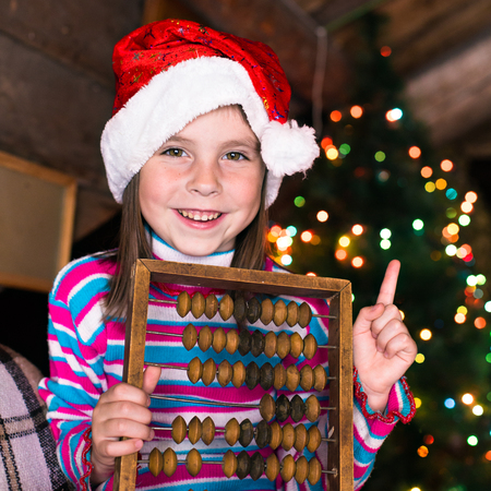 Happy child girl in a Christmas hat waiting for a miracle. Stock Photo