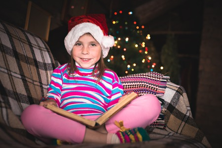 Surprised young girl in a Christmas hat with a book.