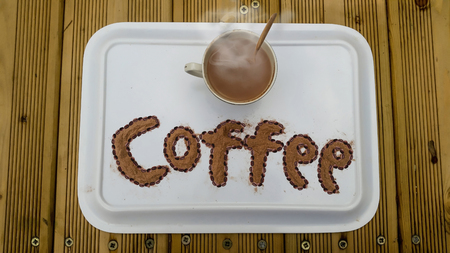 Cup of hot coffee on a wooden table with its text that has written by coffee powder and beans.