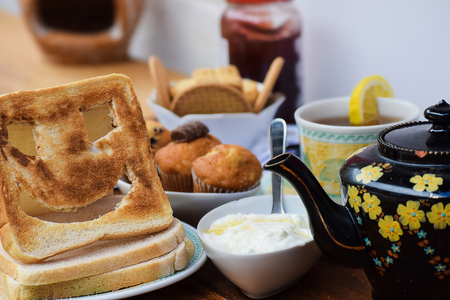 Close-up of breakfast on a brown wooden table including freshly baked blueberry muffins ,tea cup, yogurt , newspaper , teapot, cakes , biscuits and a funny smiley toast face Stock Photo