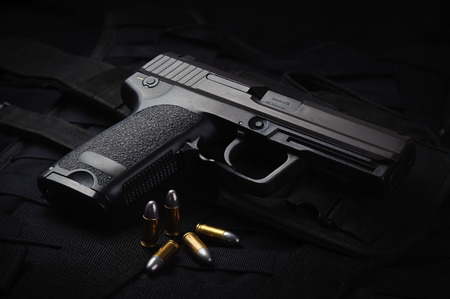 firepower: An automatic pistol laid on a tactical vest