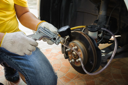 Car mechanic bleed air out of brake system Stockfoto
