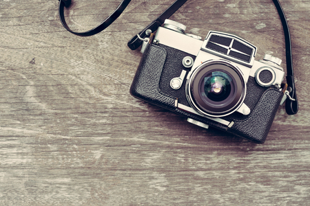 Films: A vintage camera on wooden background