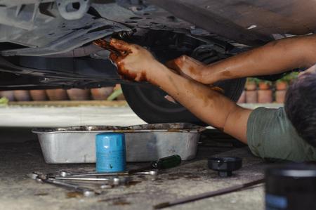 loosen: Car mechanic loosen oil filter Stock Photo