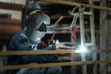 skilled labour: Worker wearing a protective mask welding metal