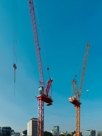 Two of construction cranes on a blue sky background