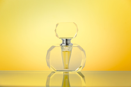 Crystal bottle on yellow gradient background. Cut glass perfume bottle.
