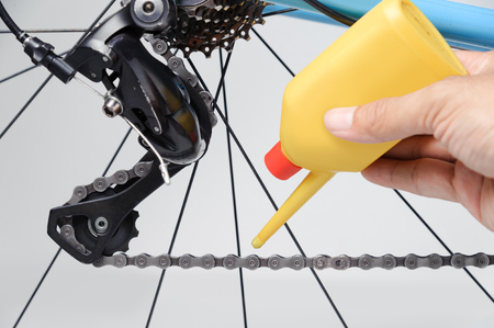Mechanic oiling bicycle chain and gear with oil.