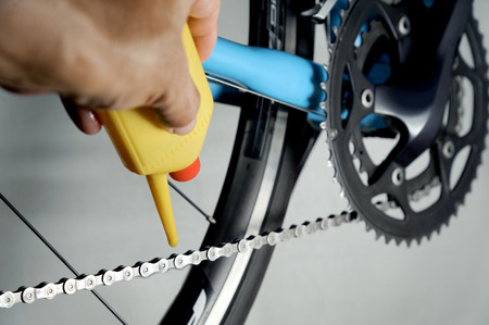 Mechanic oiling bicycle chain and gear with oil. Studio shot Standard-Bild