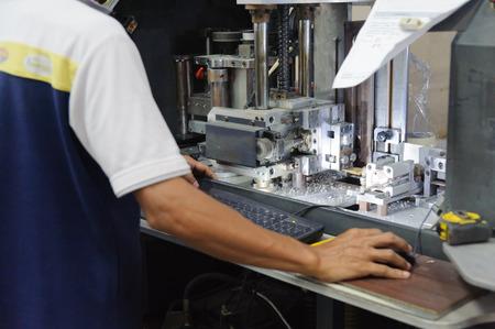 Man handling computer controlled machine in workshop Standard-Bild