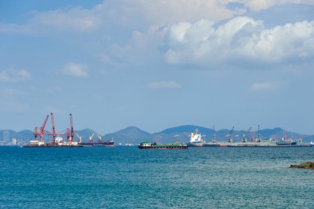 Container ships anchor along a deep seaport in daylight. Cargo crane in background