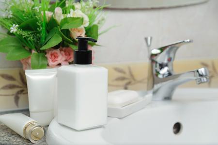 Cosmetics in a bathroom. Dispenser cream bottle and soap on a wash basin Standard-Bild