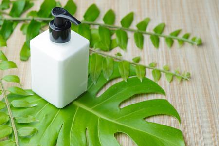 Lotion bottle with green leaf on wicker background. Dispenser cream bottle