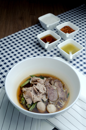 Thai traditional stewed pork soup with morning glory and bean sprout. Noodles and many kinds of sauces