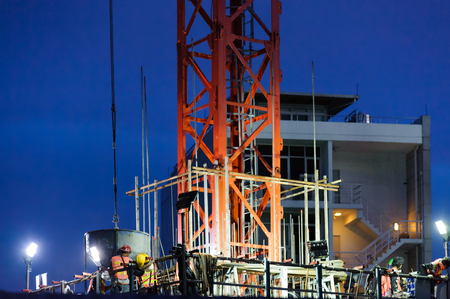 Tower crane lift cement bucket up to top of building during construction with night blue sky background