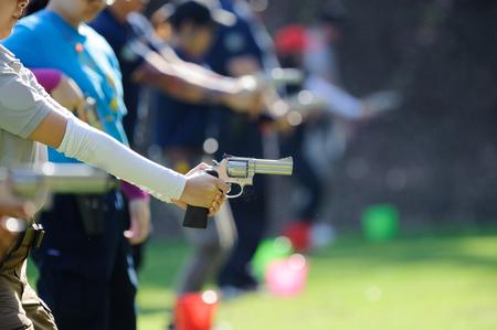 Donna che tiene la pistola e si prepara a sparare al bersaglio. Corsi di tiro difensivo Archivio Fotografico