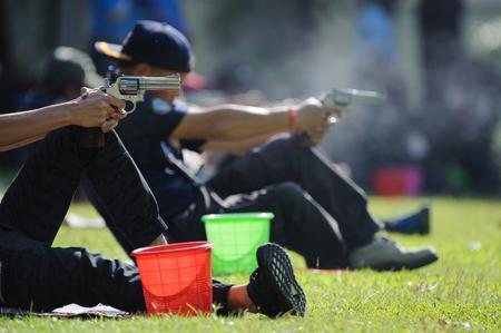 Man firing handgun at target in shooting range Standard-Bild - 120046160
