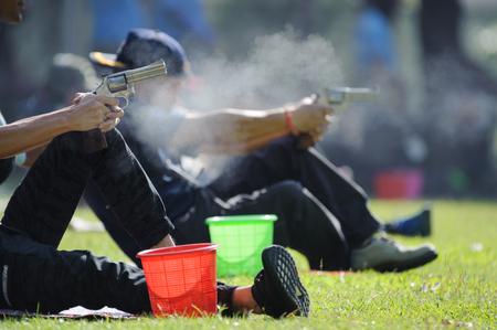 Man firing handgun at target in shooting range