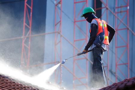 Pracownik w kamizelce odblaskowej czyszczący dachówki za pomocą myjki wysokociśnieniowej. Czyszczenie dachu strumieniem wody pod wysokim ciśnieniem