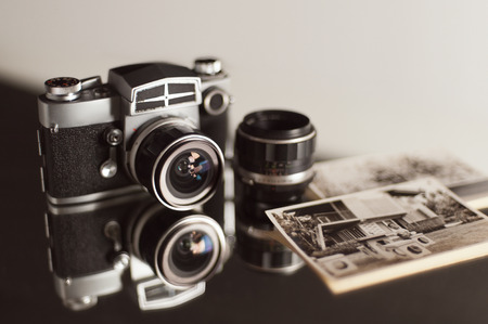 Old camera and black-and-white photos reflect on shiny table