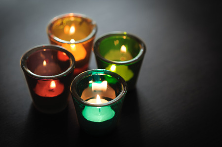 Burning candles in multi-colored glass candle holders. Decorative glass candle jars