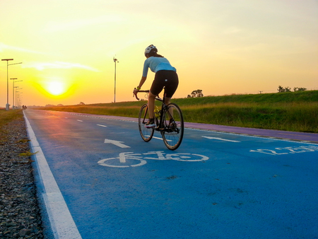 Bike path with a symbol of bike. Cyclist moving on an empty bicycle lane in sunset lights