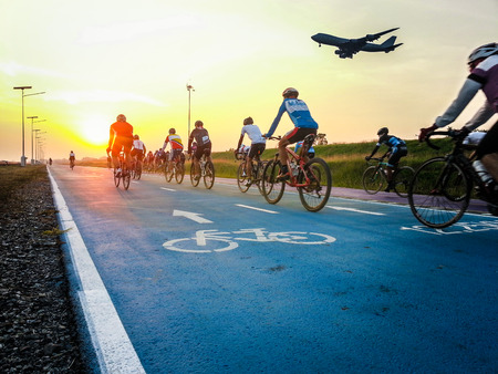 Cyclists riding bike on bicycle lane in a morning while plane landing. Bicycle lane sign on road