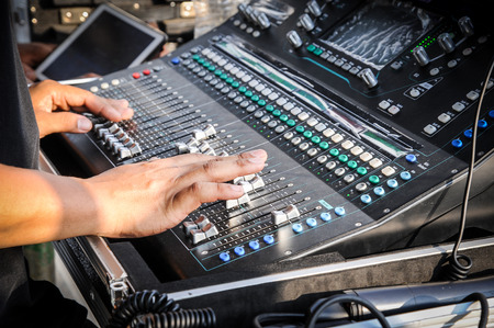 Hand adjusting on a professional audio mixer