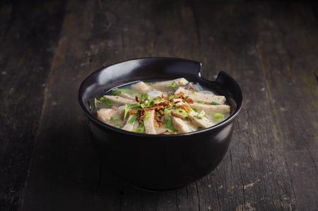 Paste of rice flour with scallion, coriander, deep fried garlic and porks on top in black porcelain bowl. Studio shot Standard-Bild