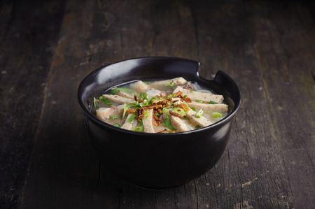 Paste of rice flour with scallion, coriander, deep fried garlic and porks on top in black porcelain bowl. Studio shot 写真素材
