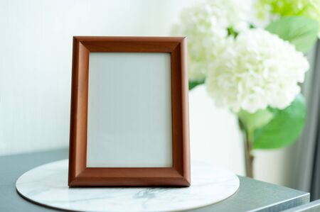 Blank wooden picture frame at the desk with bouquet at the background