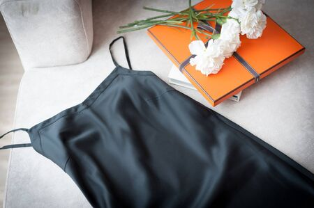 Black sexy satin pajama lay on nice looking elegance couch beside orange presents box and bouquet