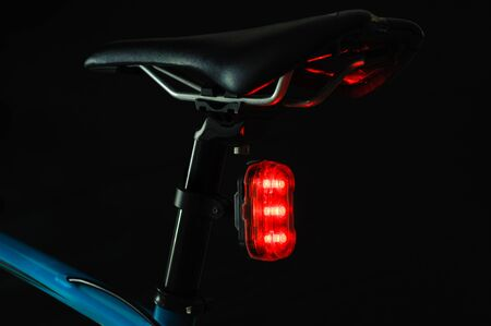 Close-up of illuminated bicycle tail light on black background