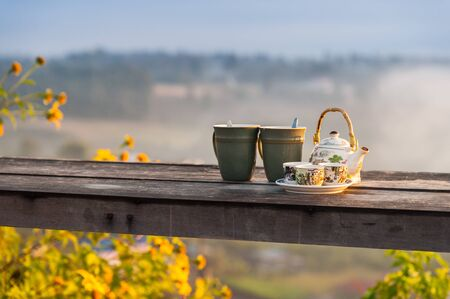 Beautiful Chinese tea set on wooden table and mountain scenery at sunrise on background