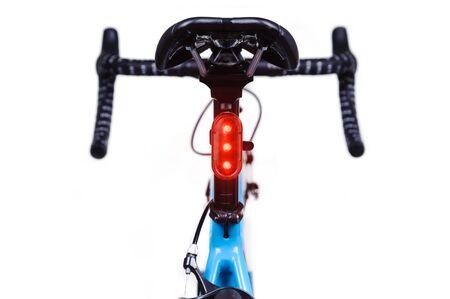 Close-up of bicycle saddle and illuminated tail light on white background Standard-Bild - 138543511