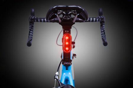 Close-up of bicycle saddle and illuminated tail light on dark background