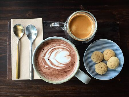 Top view of a cup of hot chocolate with latte art, espresso coffee and cookies on dark brown wooden table