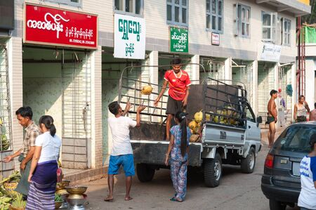 Yangon, Myanmar - Feb 13, 2018: Burmese workers move coconuts from a light truck into a store