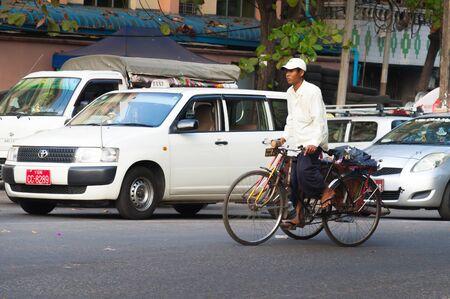 Yangon, Myanmar - Feb 13, 2018: Myanmar taxi and bicycle taxi on a road of Yangon, Myanmar