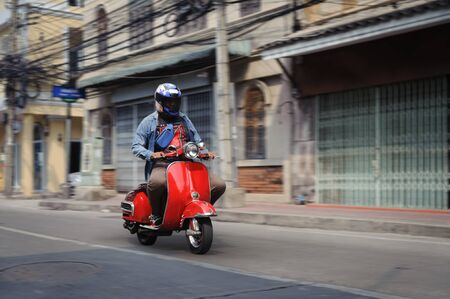 BANGKOK - JANUARY 20, 2020: Man in a full face helmet riding old red scooter on Bangkok Chinatown road 報道画像
