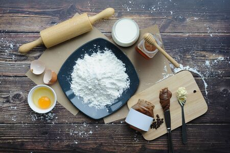 Ingredients for baking, flour, butter, eggs on a wooden background. Top view