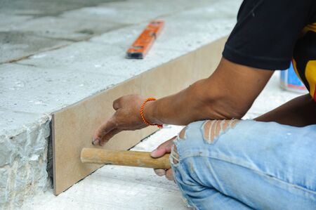 Tiler placing porcelain tile in position over adhesive. Floor tile installation Imagens