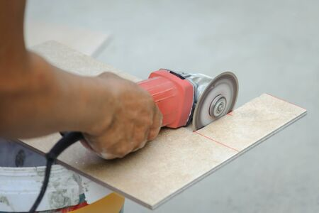 Tiler used a hand grinder machine to cut ceramic tiles.